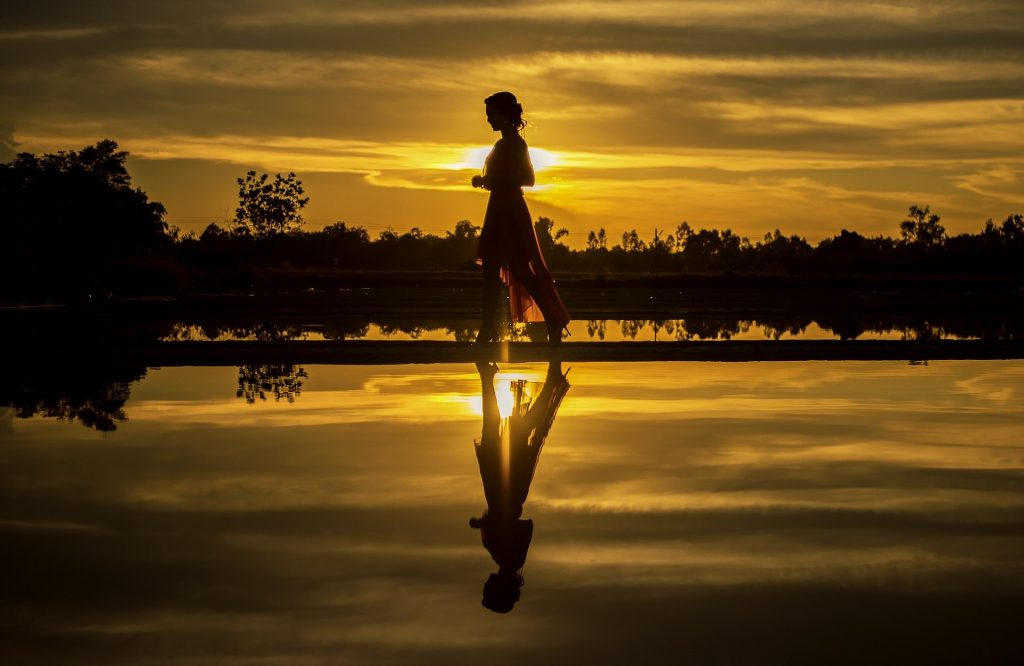 Woman walking at sunset with reflection in water.